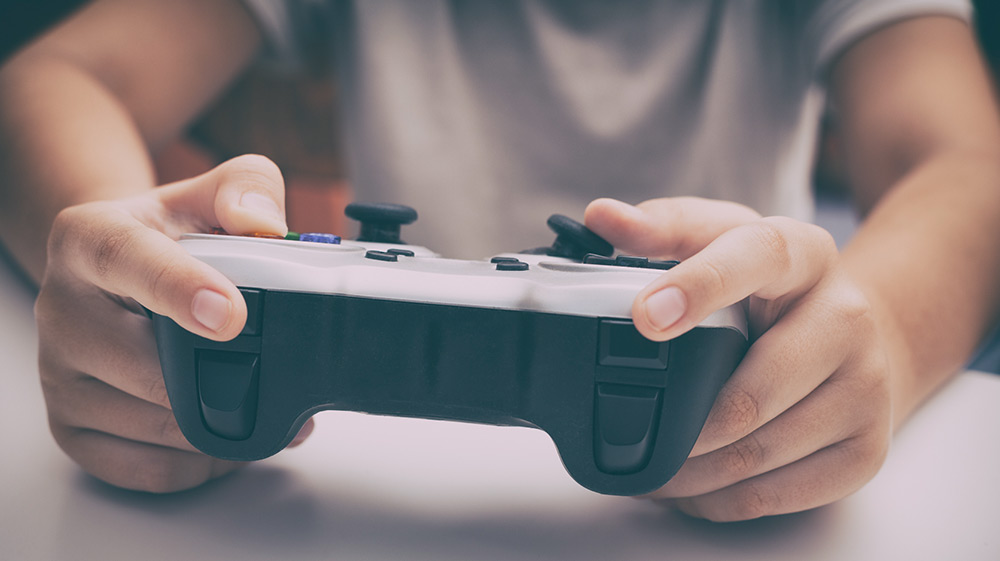 Young boy plays video game using a gamepad