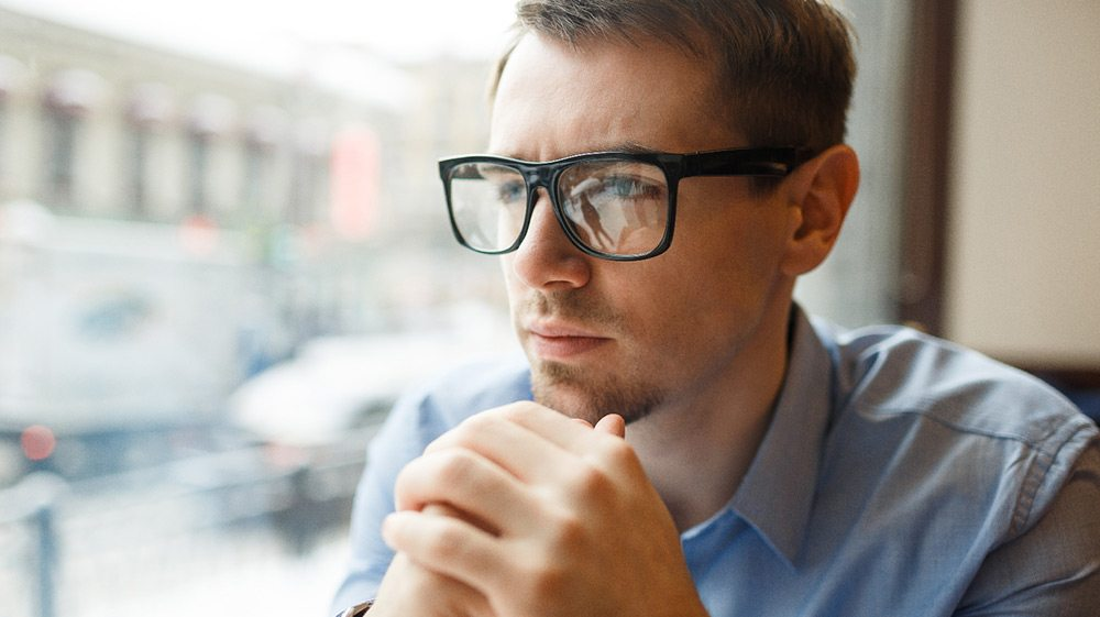 Pensive Businessman in Big Glasses Looking Out Window