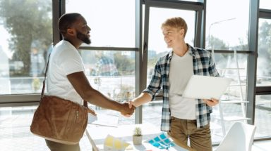 Professional young office worker holding his laptop and shaking hand of a new employee while standing in the office