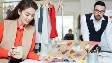 Clothing designer in clothing store sketching new designs