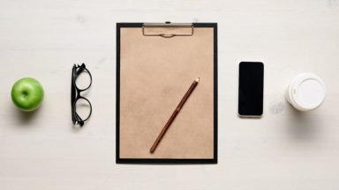 Apple, glasses, clipboard, phone, coffee mug