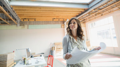 Woman smiling while holding blueprint in a new office space
