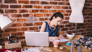 Young female fashion designer working at desk in office