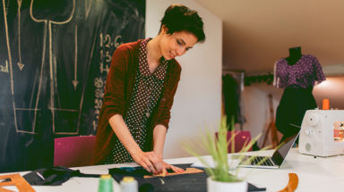 Young fashion designer is tailoring in her workshop. She is running her own small business.