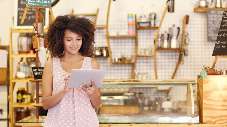 Smiling female business owner in a store, holding a tablet