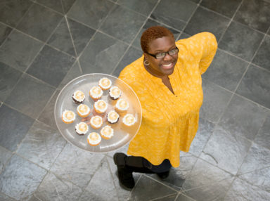 Woman holding a tray of cupcakes