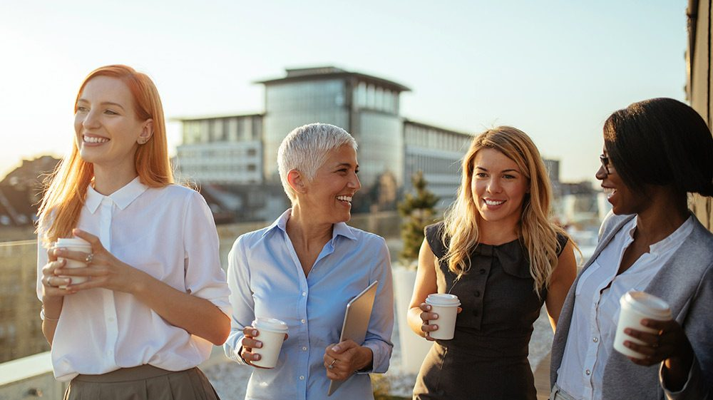 Group of women walking and drinking coffee