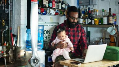 Man holding a baby while working on a computer